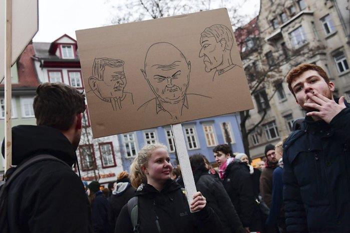 Активистка с портретами Майка Моринга из ХДС, Томаса Кеммериха (СвДП) и Бьорна Хекке из АдГ во время демонстрации в Эрфурте, Германия 06 февраля 2020 г.