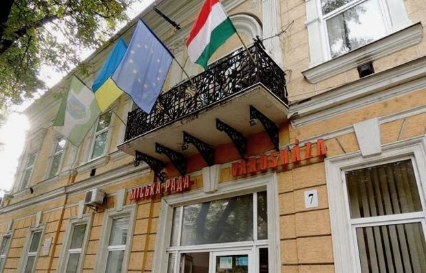 Flags on the building of the Berehove city council: the first one is the flag of the city, followed by those of Ukraine, the European Union and Hungary.