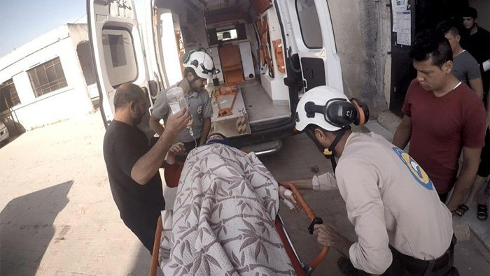 White Helms volunteers evacuate the wounded after the shelling, Idlib province, Syria