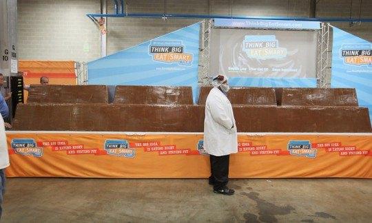 Рабочий компании «Worlds Finest Chocolate» стоит на фоне самой большой шоколадной плитки в мире