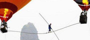Китайский акробат прошел по канату между двух воздушных шаров