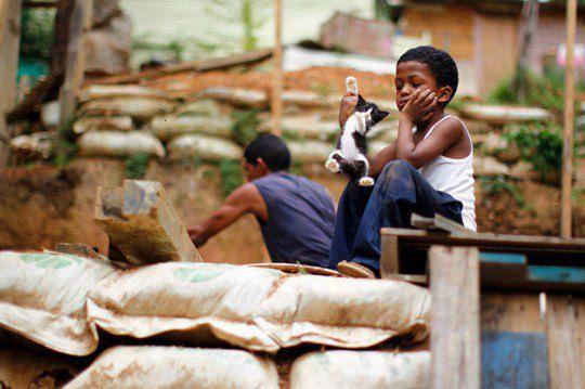 Мальчик играет с котенком, пока его отец работает над строительством их хижины в трущобе Лас Майяс в Каракасе, Венесуэла.