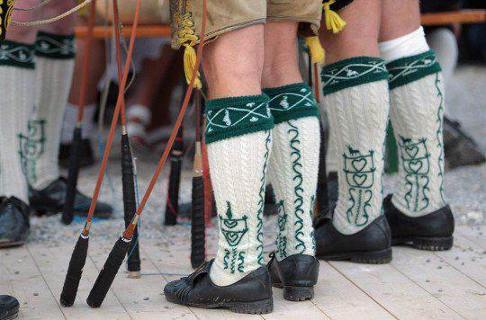 Мужчины в традиционных баварских костюмах участвуют в церемонии открытия фестиваля на лугу Терезы