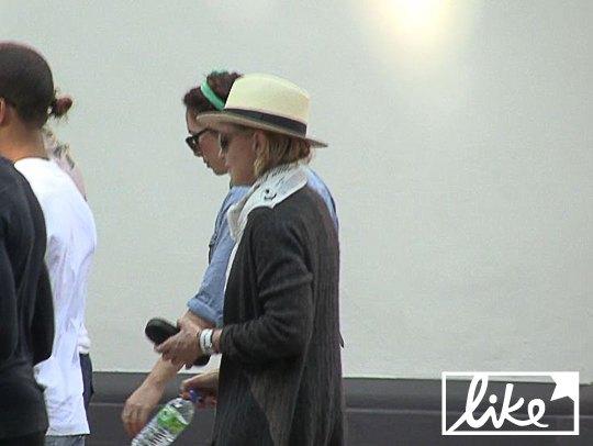 В руке Мадонна носила очки для зрения и бутылку воды
