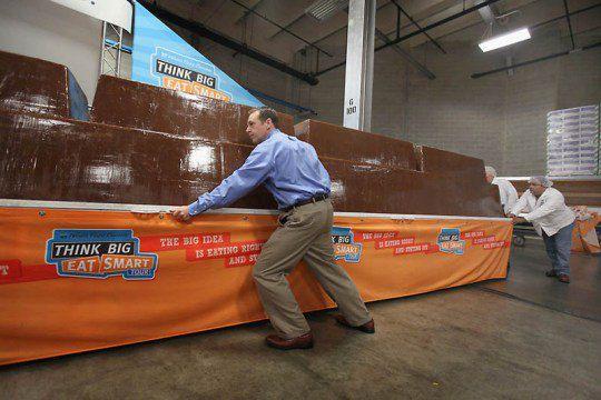Гарри Хайн (слева) и Гэри Уайчоки помогают передвинуть огромную плитку шоколада