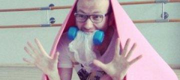Сын Повалий занимается в спортзале с гантелей в зубах