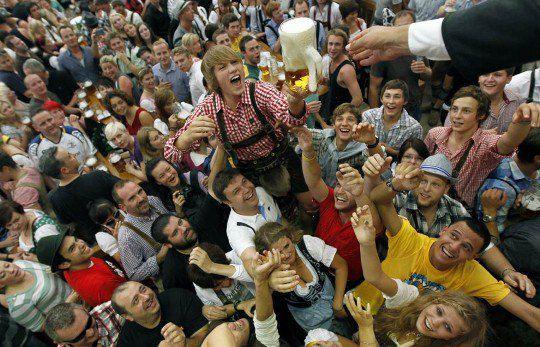 Люди тянутся за бокалом пива в палатке Hofbraeuhaus после открытия знаменитого баварского фестиваля «Октоберфест»