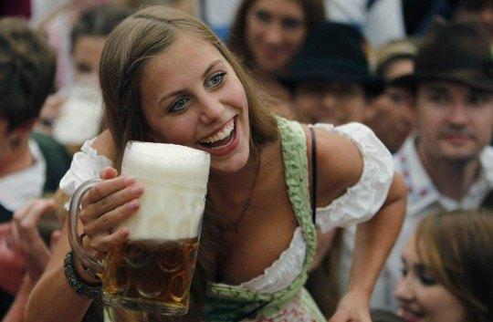 Девушка позирует с бокалом пива в палатке Hofbraeuhaus после открытия знаменитого баварского фестиваля пива «Октоберфест» в Мюнхене на юге Германии